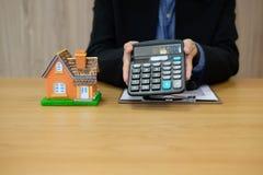 агент риэлтора с номером цены показа модели дома на калькуляторе покупка арендующ свойство Страхование недвижимости стоковая фотография rf