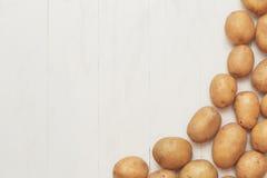 Аграрная деревенская предпосылка - сбор картошки на деревянной белой таблице Стоковая Фотография