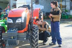 Аграрные механики проверяя условие тракторов перед сбором стоковые изображения rf