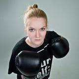 Агрессивная девушка подростка с перчатками коробки на серой предпосылке Стоковые Изображения