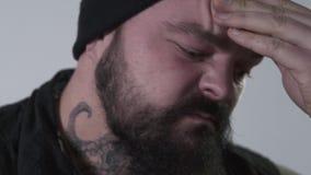 Агрессивный бородатый человек тереть его лоб для того чтобы держать назад эмоции Зверский парень с татуировками на его шеи и руке сток-видео