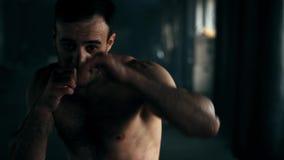 Агрессивный профессиональный бокс тени тренировки бойца бросая порочное дуновение Молодой чемпион практикует коробку на a видеоматериал