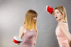 2 агрессивных женщины воюя используя ботинки Стоковое Фото