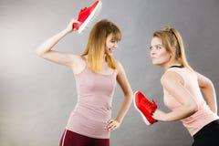 2 агрессивных женщины воюя используя ботинки Стоковые Фото