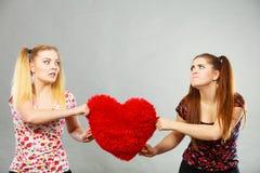 2 агрессивных женщины имея спорят бой держа сердце Стоковая Фотография RF