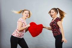 2 агрессивных женщины имея спорят бой держа сердце Стоковое фото RF