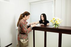 Администратор молодой женщины в зубоврачебной клинике в рабочем месте Допущение клиента стоковые изображения