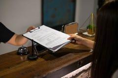 Администратор отправленный документами в гостя для подписания и заполнять вверх по процессу регистрации формы Концепция гостиницы стоковое фото