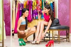 Азиатская дама продаж в ботинках магазина предлагая стоковое изображение