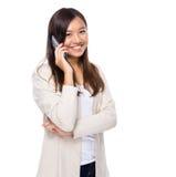 Азиатская беседа женщины к мобильному телефону Стоковое фото RF