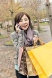 Азиатская беседа женщины на хозяйственных сумках владением телефона стоковое изображение