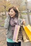 Азиатская беседа женщины на хозяйственных сумках владением телефона стоковое фото