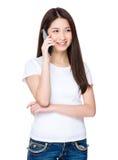 Азиатская беседа молодой женщины к мобильному телефону Стоковое фото RF