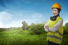 Азиатская бизнес-леди нося желтую улыбку шлема стоковое фото rf