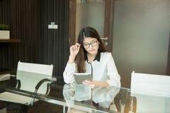 Азиатская бизнес-леди используя таблетку в офисе Стоковые Фотографии RF