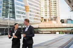 Азиатская бизнес-леди и кавказский бизнесмен идя совместно в город и беседу о будущем дела Стоковые Изображения