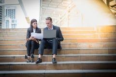 Азиатская бизнес-леди и кавказский бизнесмен сидят на лестнице и держат бумагу отчета о продажи с компьтер-книжкой Стоковые Фото