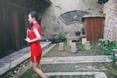 Азиатская восточная восточная китайская красота женщины в cheongsam традиционного старого костюма платья красном с вентилятором в стоковые изображения