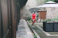 Азиатская восточная восточная китайская красота женщины в cheongsam традиционного старого костюма платья красном с вентилятором в стоковые фото