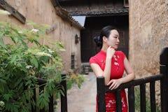 Азиатская восточная восточная китайская красота женщины в cheongsam традиционного старого костюма платья красном в загородке сада стоковые фотографии rf