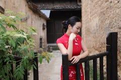Азиатская восточная восточная китайская красота женщины в cheongsam традиционного старого костюма платья красном в загородке сада стоковая фотография