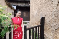 Азиатская восточная восточная китайская красота женщины в cheongsam традиционного старого костюма платья красном в загородке сада стоковое изображение