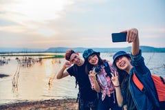 Азиатская группа в составе молодые люди с друзьями и рюкзаками идя совместно и счастливые друзья принимают фото и selfie, ослабля стоковое изображение rf