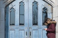 Азиатская дама играет ее мобильный телефон перед дверью Добавленный фильтр Стоковые Изображения RF
