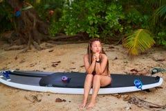 Азиатская девушка в афро отрезках провода сидя на пляже на доске, смотря прочь стоковое изображение