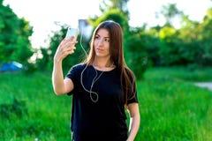 Азиатская девушка в лете в парке красивейшее брюнет Усмехающся и смотрящ телефон слушая к музыке Посылает голос Стоковое фото RF