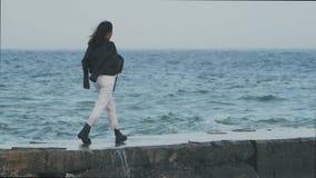 Азиатская девушка в солнечных очках морем ветер начинает hairasian рост девушки полностью идет к пристани на предпосылке моря сток-видео