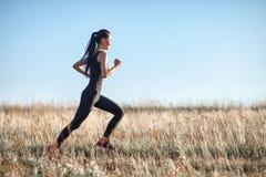 Азиатская девушка в sportswear бежать через поле, разминку утра Стоковая Фотография