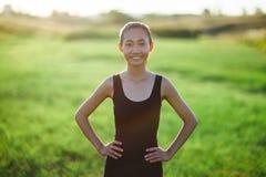 Азиатская девушка в sportswear бежать через поле, разминку утра Стоковое Изображение RF