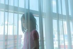 Азиатская девушка играя за отвесным занавесом большим окном с e стоковые изображения rf