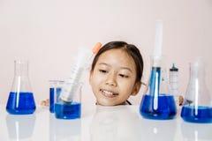 Азиатская девушка играя как ученый для того чтобы экспериментировать Стоковые Фото