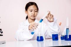 Азиатская девушка играя как ученый для того чтобы экспериментировать Стоковое фото RF