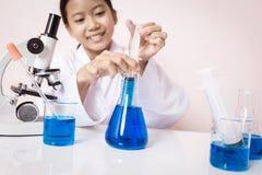 Азиатская девушка играя как ученый для того чтобы экспериментировать Стоковые Фотографии RF