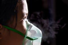 Азиатская девушка имеет астму или nebulization заболеванием и потребностью пневмонии мимо получает маску ингалятора на ее стороне стоковая фотография rf