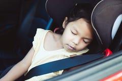 Азиатская девушка маленького ребенка сидя в автокресле и спать стоковые фотографии rf