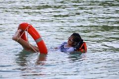 Азиатская девушка наслаждается поплавать и томбуй жизни стоковое изображение rf