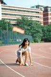Азиатская девушка на взлётно-посадочная дорожка в спортивной площадке школы Стоковое Фото