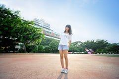 Азиатская девушка на взлётно-посадочная дорожка в спортивной площадке школы Стоковые Изображения