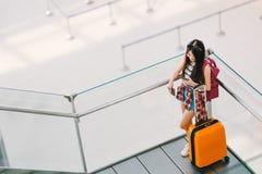 Азиатская девушка путешественника, студент колледжа используя звонок smartphone или болтовню на авиапорте с багажом, рюкзаком Сет стоковые фотографии rf