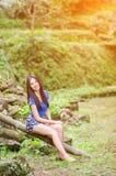 Азиатская девушка сидит вниз путь в бамбуковом лесе Стоковое Изображение