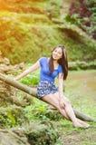 Азиатская девушка сидит вниз путь в бамбуковом лесе Стоковые Изображения RF