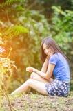 Азиатская девушка сидит вниз путь в бамбуковом лесе Стоковые Фотографии RF