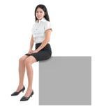 Азиатская девушка сидя на пустой афише Стоковое Изображение RF