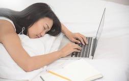 Азиатская девушка спать с компьтер-книжкой на ее кровати Стоковое Изображение