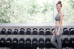 Азиатская девушка спорта стоя перед разминкой i полки гантелей Стоковые Изображения