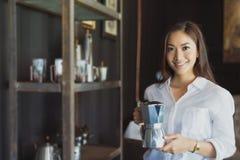 Азиатская девушка стоя держащ улыбку бака кофе и имеет потеху реальную Стоковое фото RF